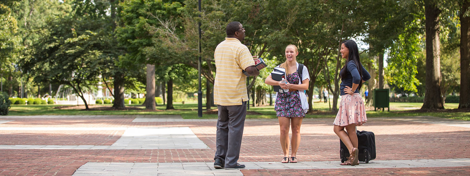 A group chats at the library plaza of Regent University, Virginia Beach.