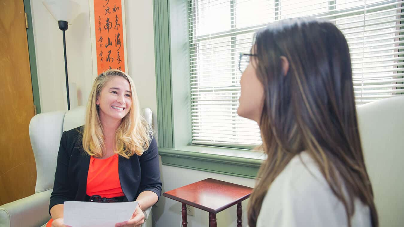 Two graduates interact: Explore Regent's online MA in Human Services - Human Services Counseling program.