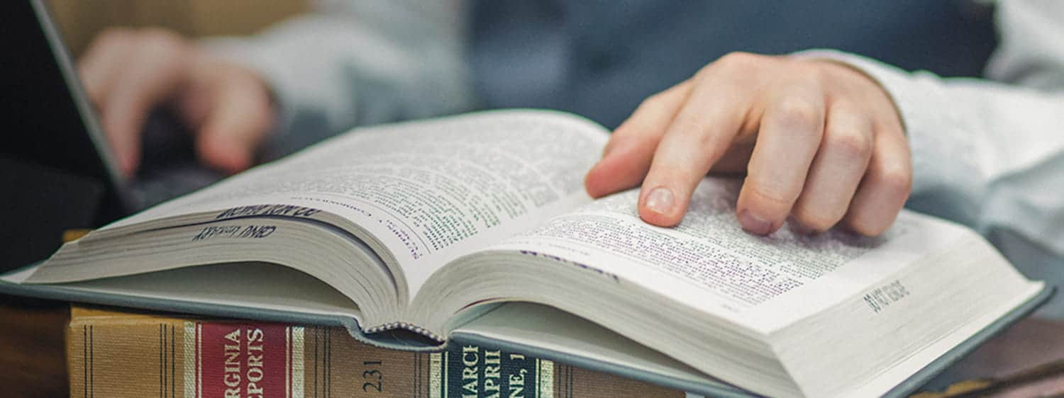 An student's finger on an open book: Pursue an MDiv Biblical Languages degree online or on campus at Regent University, VA 23464.