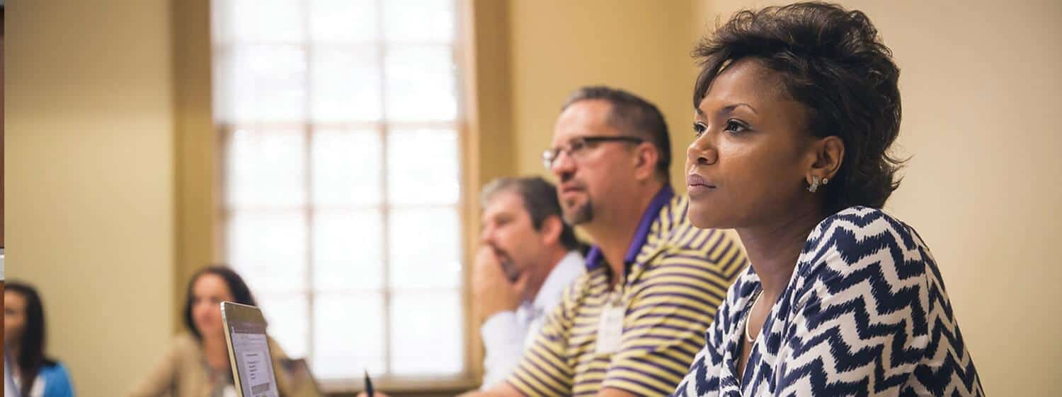 Students in a classroom: Pursue an online Ph.D. in Organizational Leadership at Regent University.