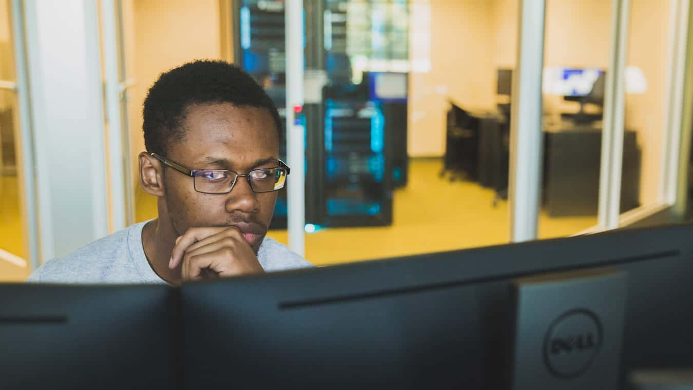 A student looks at his computer screen: Pursue your B.S. in Cyber and Digital Forensics degree online at Regent University, Virginia Beach.