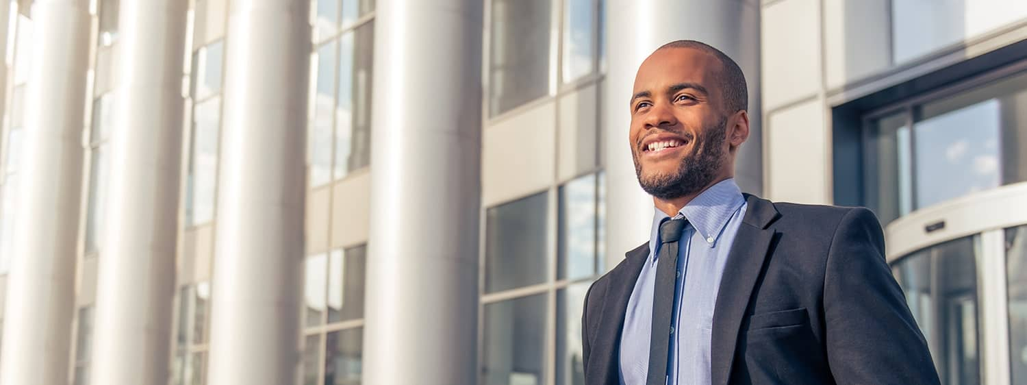A professional outside an office building: Explore the Bachelor of Science in Accounting degree program offered by Regent University.