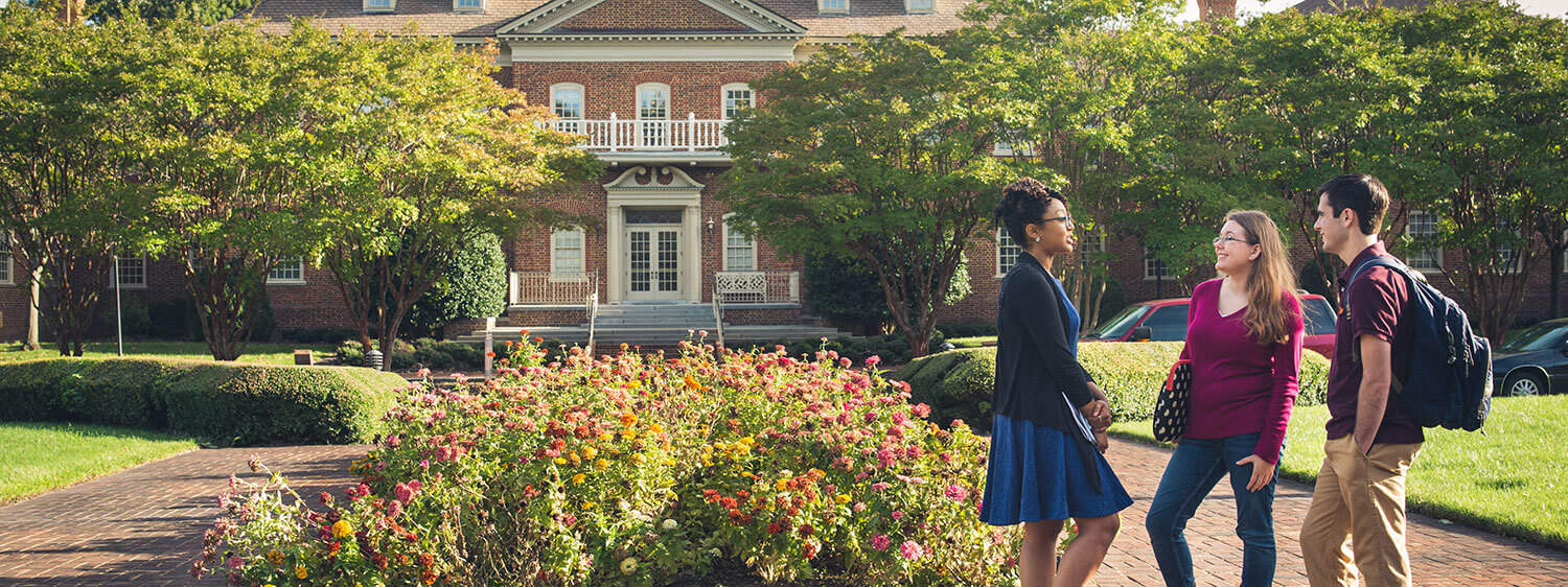 Students chat outside the Classroom Building of Regent University, Virginia Beach.