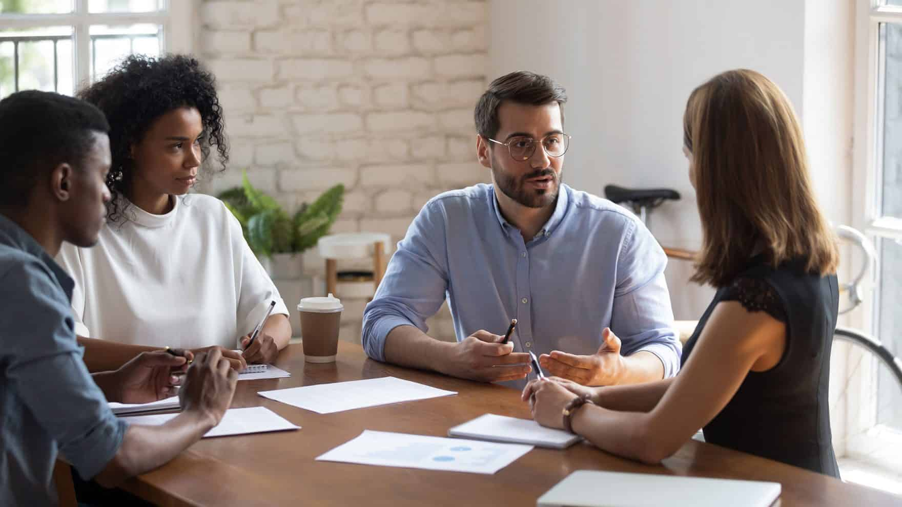 A person talking to a group: Explore leadership coaching.