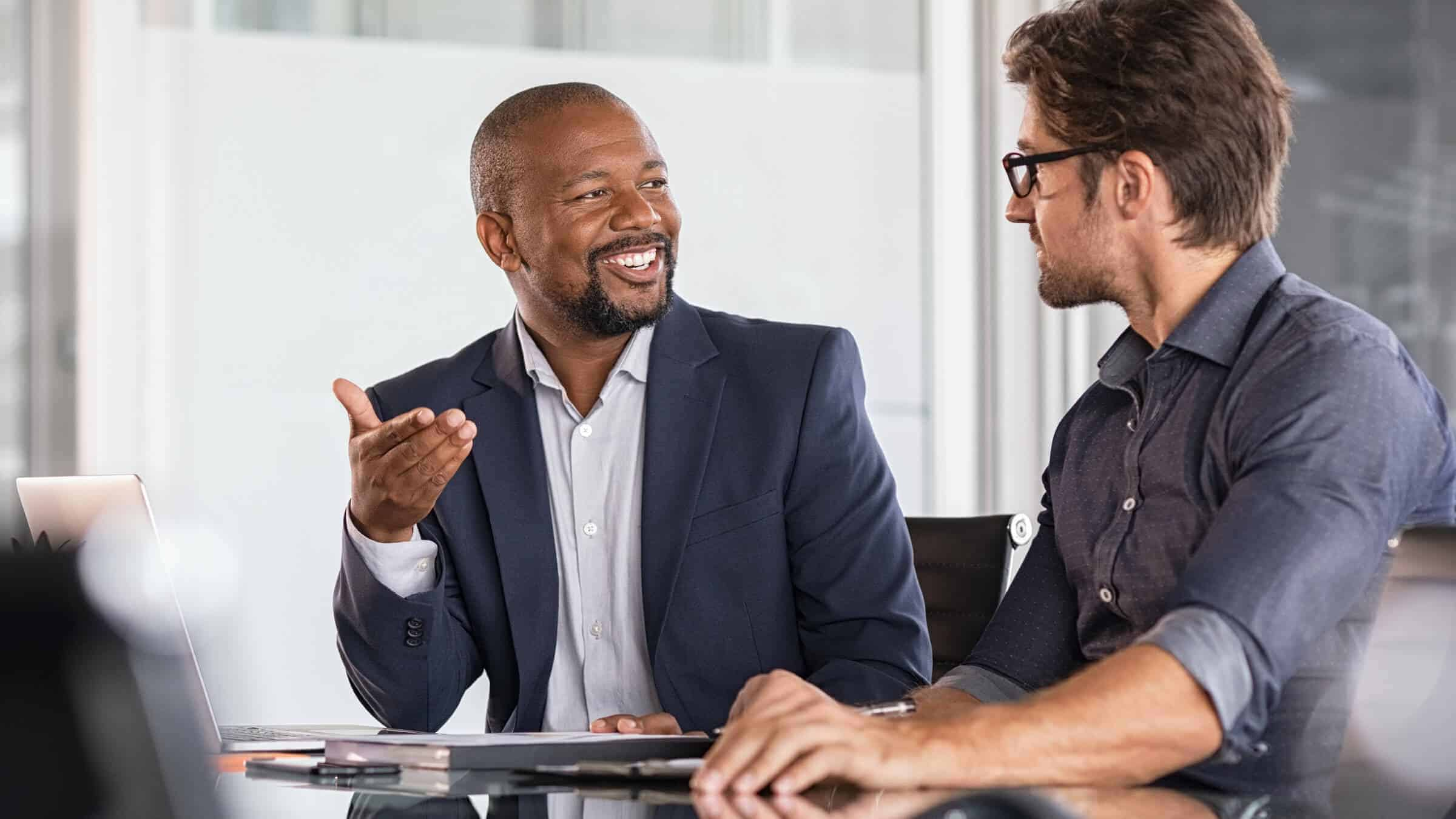 Two executives in a conversation: Advance your career through Regent's MBA, online or in Virginia Beach.