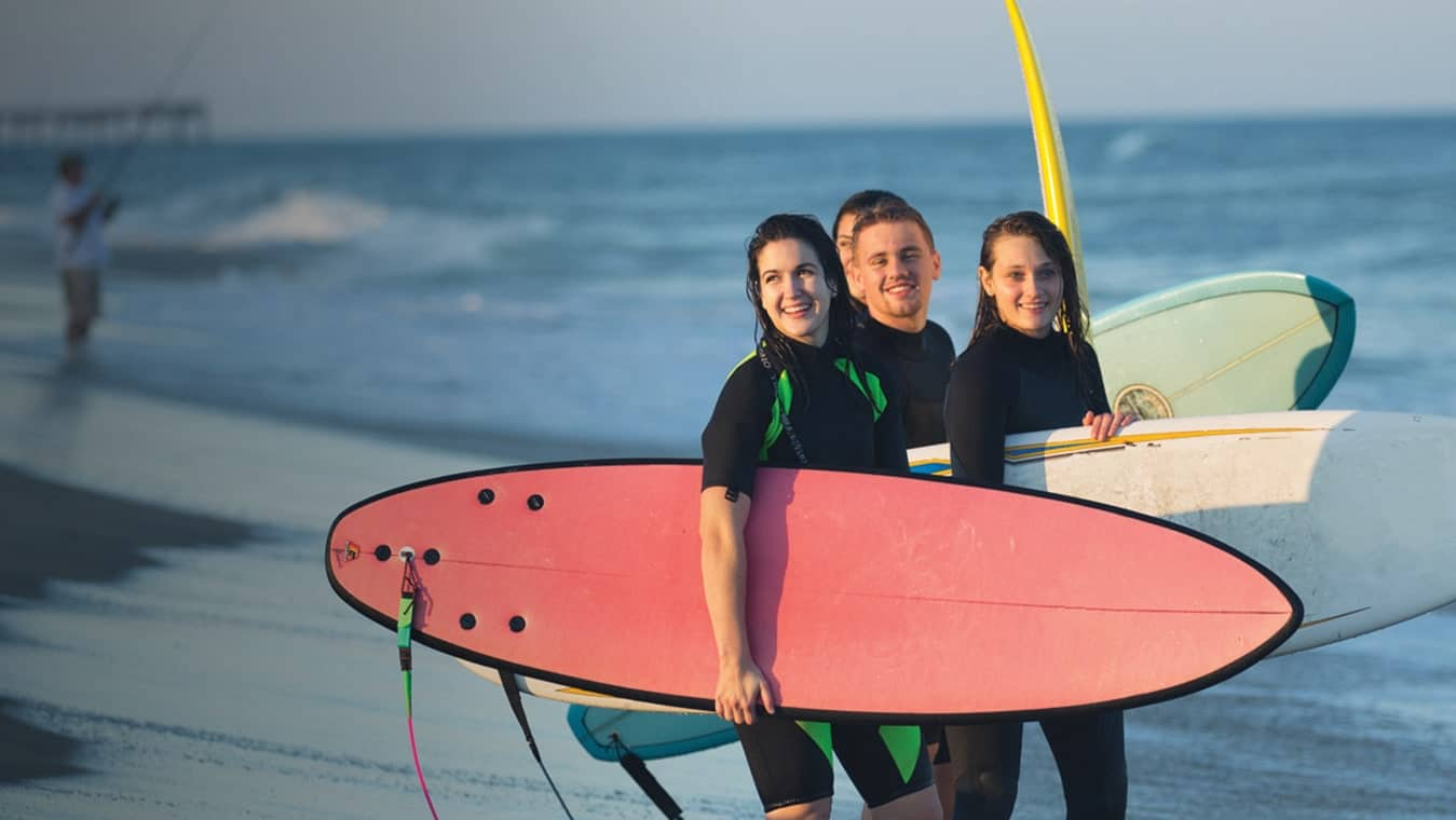 Regent's college students with surfboards at the beach.
